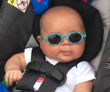 A baby sitting in a carseat wearing sunglasses
